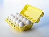 Ten white eggs in open egg box