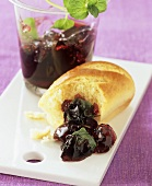 Raspberry and redcurrant jelly on a board with bread roll