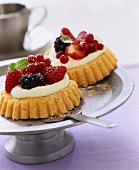 Two small berry flans with vanilla cream