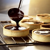 Making biscuits (filling pastry cases with chocolate sauce)
