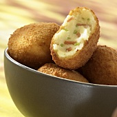 Potato croquettes with ham filling, one halved
