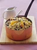 Couscous salad with orange segments and sultanas in pan