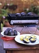 Gegrillte Avocadohälften auf einem Teller und auf dem Grill