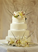 Decorated, four-tier wedding cake with lilies