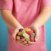 Verschiedene Fruchtgummibonbons, von Händen gehalten