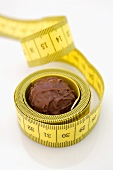 Chocolate truffle lying in rolled-up tape measure