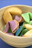 Different-coloured fortune cookies in wooden bowl