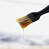 Olive oil dripping from a pastry brush