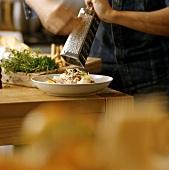Grating Parmesan over pasta dish