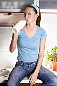 Young woman drinking out of milk bottle in kitchen