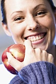 Laughing woman holding an apple