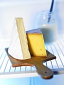 Pieces of cheese on a board in fridge