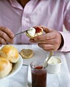 Mann schmiert sich Scone mit Clotted Cream & Marmelade