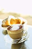Hot chocolate with milk froth and a croissant
