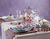 Laid Easter table with cakes and Easter eggs