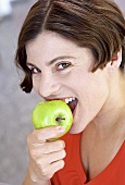 Young woman biting into an apple