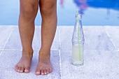 Kleines Kind steht am Beckenrand mit einer Flasche Limonade