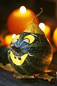 Green pumpkin with carved smiling face