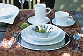 Place-setting with white tableware on a garden table