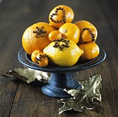 Citrus fruit studded with cloves in a bowl