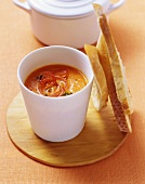 Red pepper soup with thyme in white beaker