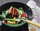 Vegetable curry with roasted duck breast & Thai basil in wok