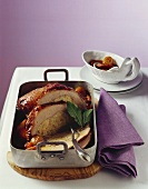Stuffed veal breast with braised vegetables in roasting tin