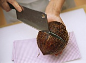 Cutting open a coconut with a cleaver