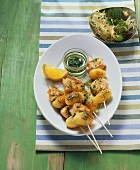 Potato and salmon skewers with pesto and salad