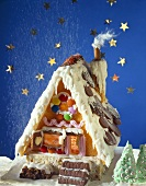 Icing sugar snow falling onto a gingerbread house