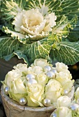 Autumn decoration: white roses & ornamental cabbage (edible)