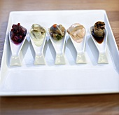 Assorted herring appetisers on spoons