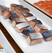 Lightly-cooked salmon pieces on white serving platter