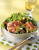 Goat's cheese wrapped in bacon on salad leaves