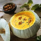 Pumpkin cream soup served in hollowed-out pumpkin