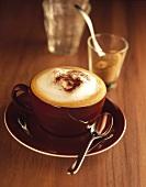 Cappucchino in brauner Tasse, dahinter Zucker im Glas