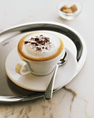 Cappuccino in white cup and saucer on stainless steel tray