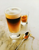 Glass of latte macchiato and a spoon with brown sugar