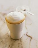 Latte macchiato in white pottery beaker