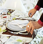 Hands placing cutlery at a place-setting