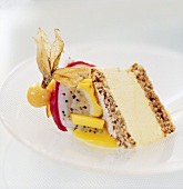 A piece of mango ice cream cake with nut sponge and fruit