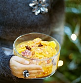 Woman holding bowl of blood orange salad