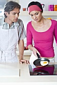 Man and woman frying an egg on hob