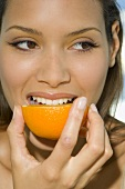 Woman biting into half an orange