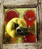 Three jars of quince jelly and a fresh quince
