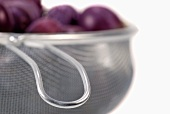 Plums in a metal sieve