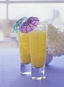Orange Velvet in two glasses with cocktail umbrellas