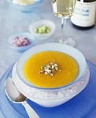 Chilled carrot cream soup with diced cucumber and onion