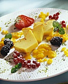 Slice of quark cake with mango sauce and fresh berries