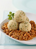 Small bread dumplings on carrot bolognese